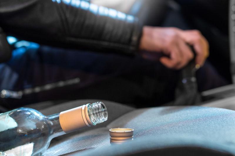 Young man driving car under the influence of alcohol. Hand on gear stick. Close up of empty bottle of wine on front seat. Traffic safety risk.